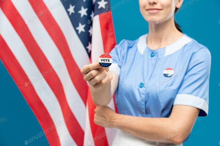 Young room-maid in uniform showing you vote insignia against stars-and-stripes