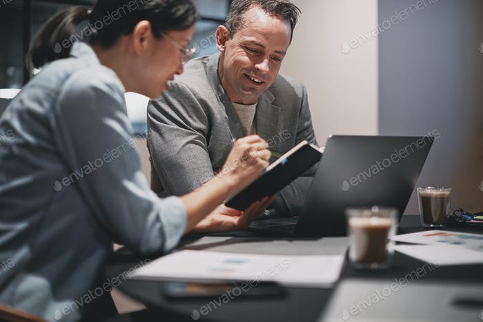 Two smiling businesspeople discussing notes together at an office table