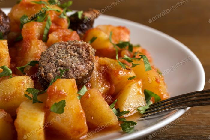 Potatoes stew with pork sausages