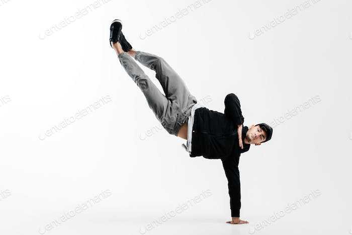 Stylish young man is dancing breakdance. He is standing on one arm and lifting both legs up