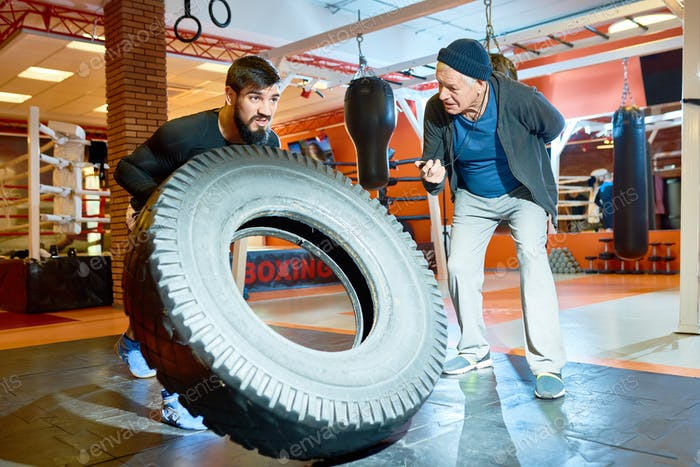 Sportsman flipping tyre with coach near