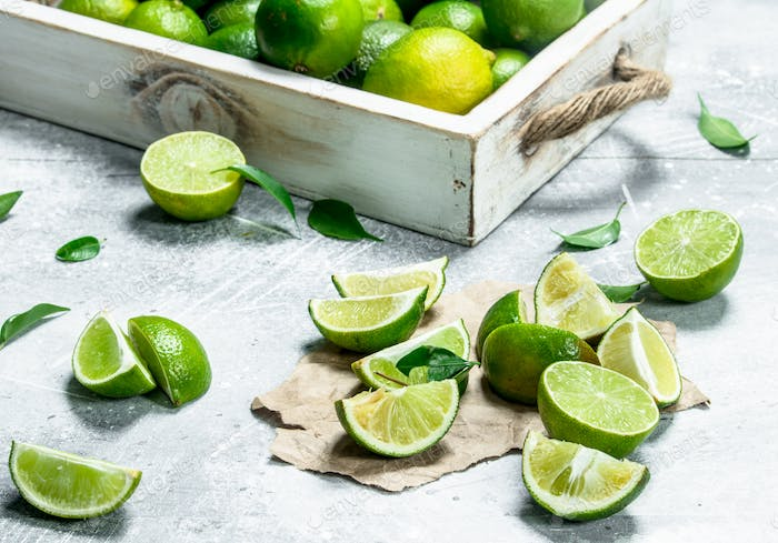 Fresh lime on tray and lime slices on paper.