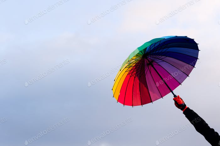 Umbrella in hand against sky background