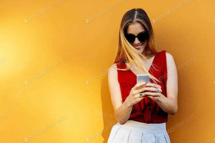 Portrait of beautiful young woman using mobile phone in the street.