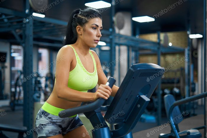 Fit woman using exercise bike