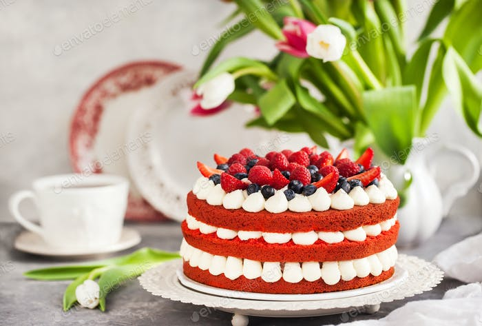 Delicious homemade red velvet cake decorated with cream and fres