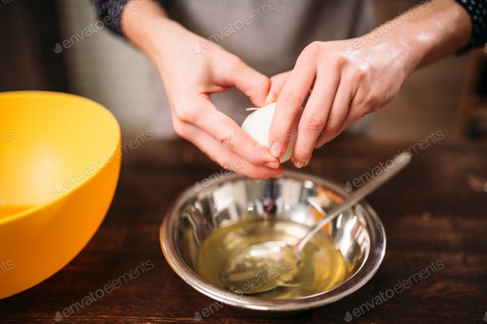 Female hands breaks the egg into a bowl