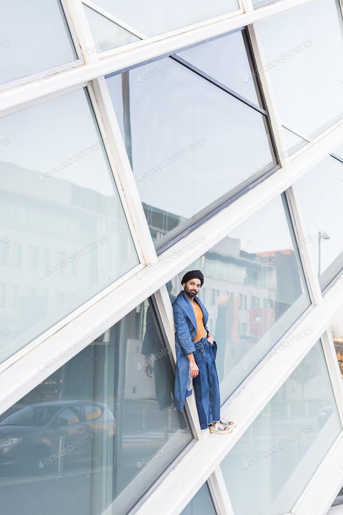 Junger indischer Mann posiert in einem urbanen Kontext