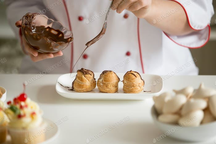 Close up of professional confectioner hands glazing profiteroles