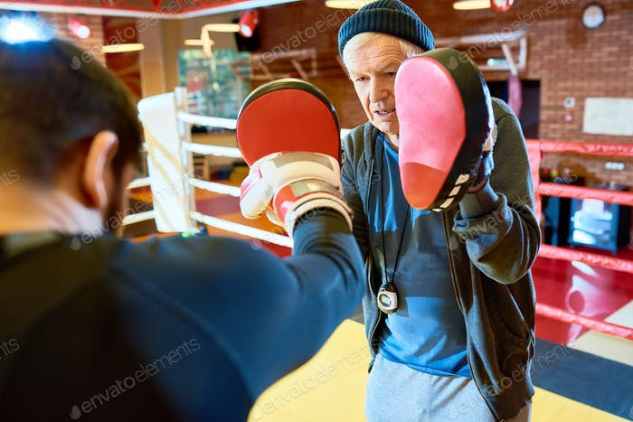 Man punching focus mitts with coach