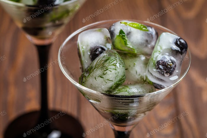 Ice cubes with dill, estragon and blueberry