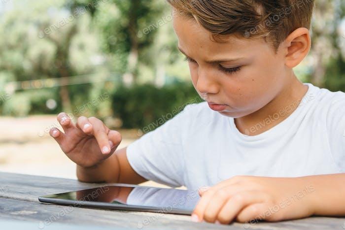 Kid tocando la tableta en el jardín