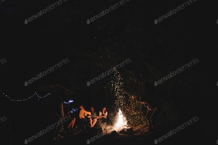 Hipster man playing on acoustic guitar and singing song with friends travelers at big bonfire