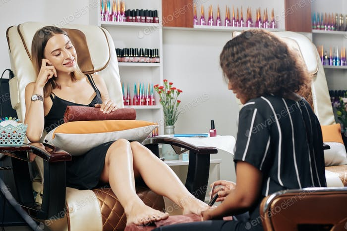 Lovely woman enjoying pedicure process