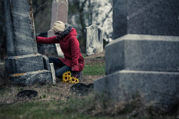 Sad Woman in Mourning Touching a loved one's Gravestone