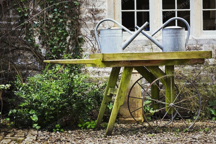 Old fashioned wooden wheel barrow and tin watering cans in the garden of an old house.