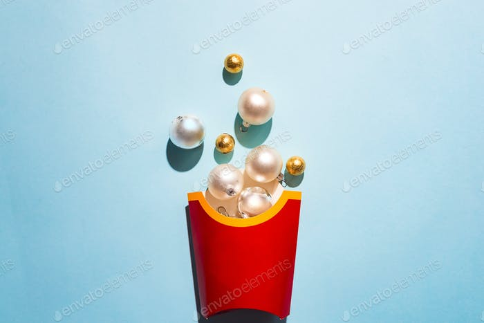 Blank french fries box with white New Year's balls on a blue paper background,