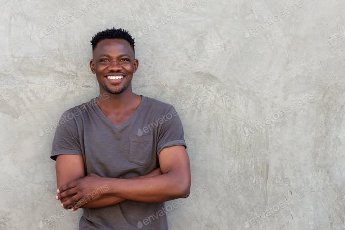 happy african man smiling with arms crossed by wall