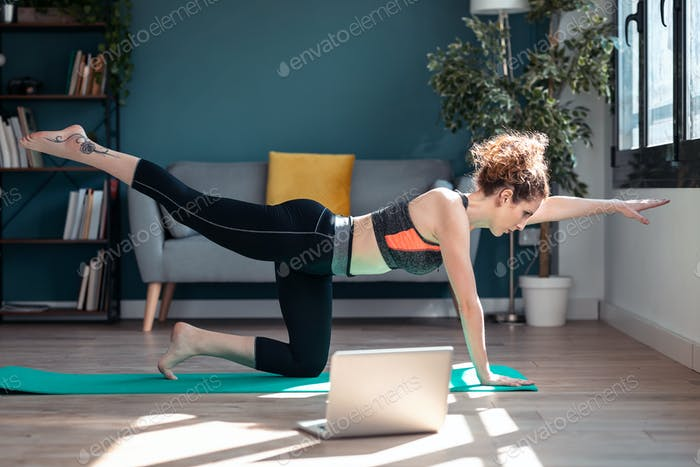 Sporty young woman doing hypopressive exercises following online gym classes via laptop at home.
