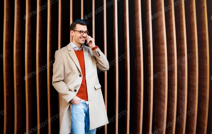 Young man with smartphone standing against wooden wall.
