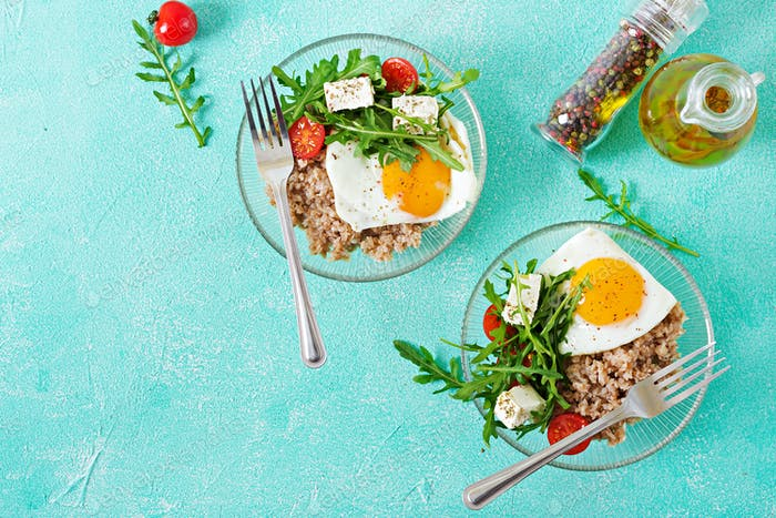 Healthy breakfast with egg, feta cheese, arugula, tomatoes  and buckwheat porridge