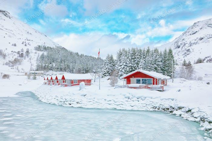 Wunderbare Winterlandschaft mit traditionellen norwegischen roten Holzhäusern am Ufer