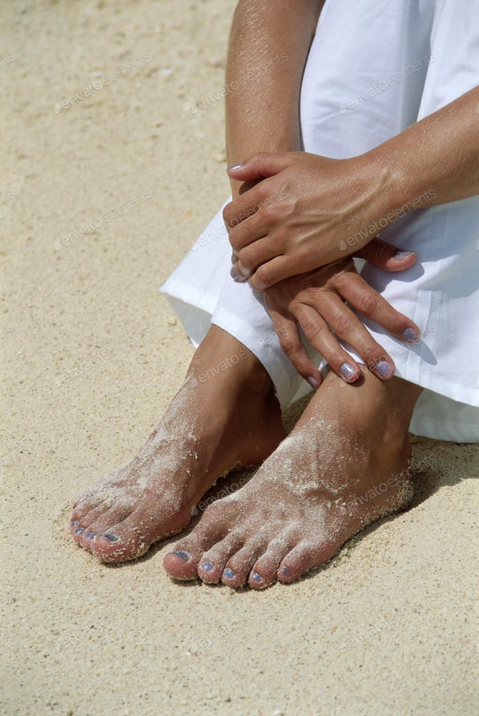 Young woman's feet covered in sand