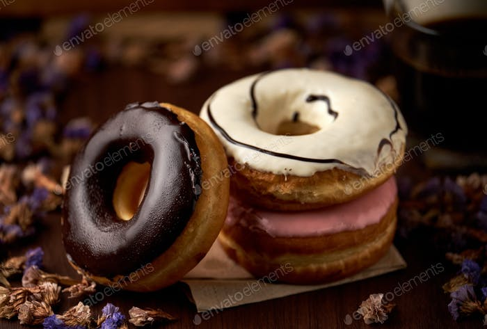 The sweet glazed donuts stacked on the table