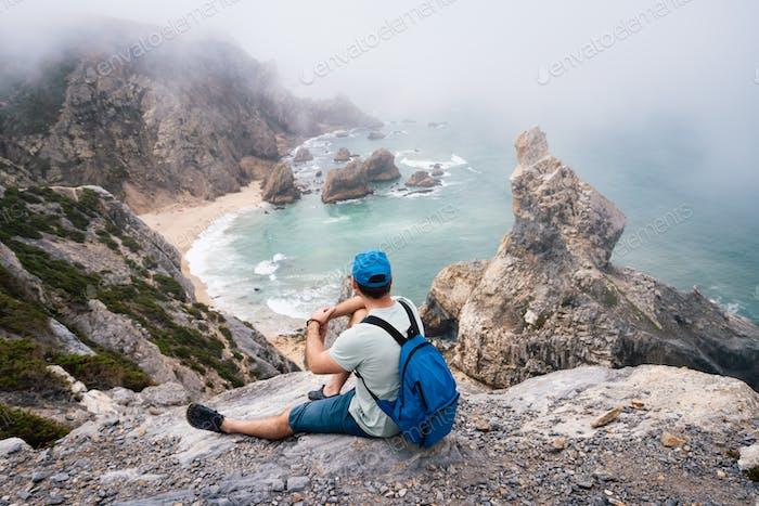 Adult male with backpack resting at stone edge of Praia da Ursa Beach coastline. Surreal scenery