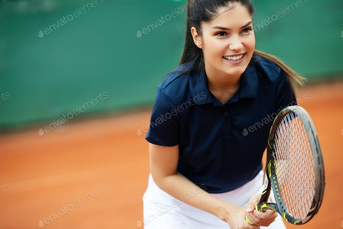 Woman tennis player smiling while holding the racket during tennis match