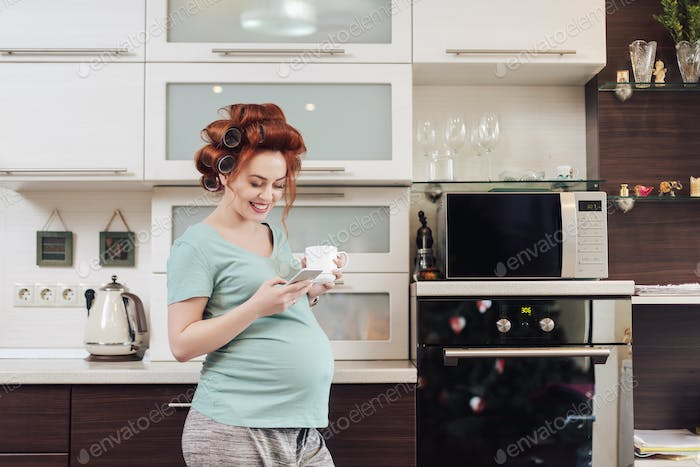 Smiling pregnant woman using a smartphone