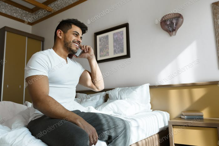 Cheerful guy talking on phone in bed