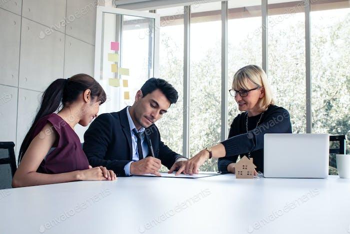 Mann und Frau beraten sich mit dem Eigentümer über den Hausverkaufsvertrag.
