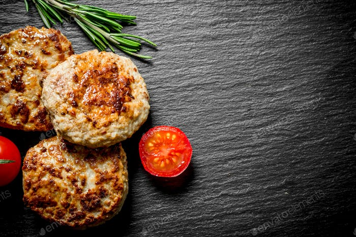 Cutlets with rosemary and tomatoes.