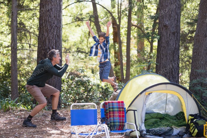 Father photographing playful boy jumping at campsite
