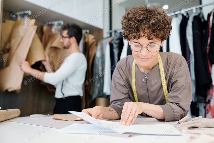 Young Female Seamstress Or Fashion Designer Looking At Sketch Of New Model Photo By Pressmaster On Envato Elements