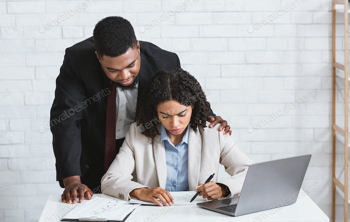 Stop sexual harassment. Perverted African American boss touching his attractive female assistant at