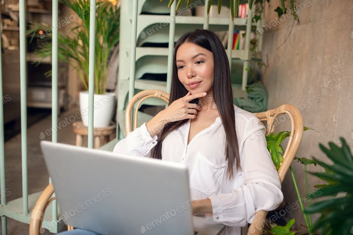 Young businesswoman feeling thoughtful while reading e-mail