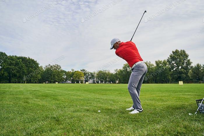 Sportsman practicing swings on the driving range