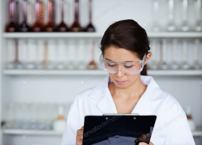 Scientist writing on a clipboard
