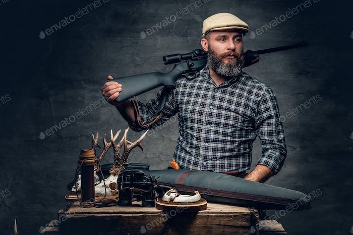 Bearded traditional hunter with his trophy holds a rifle.