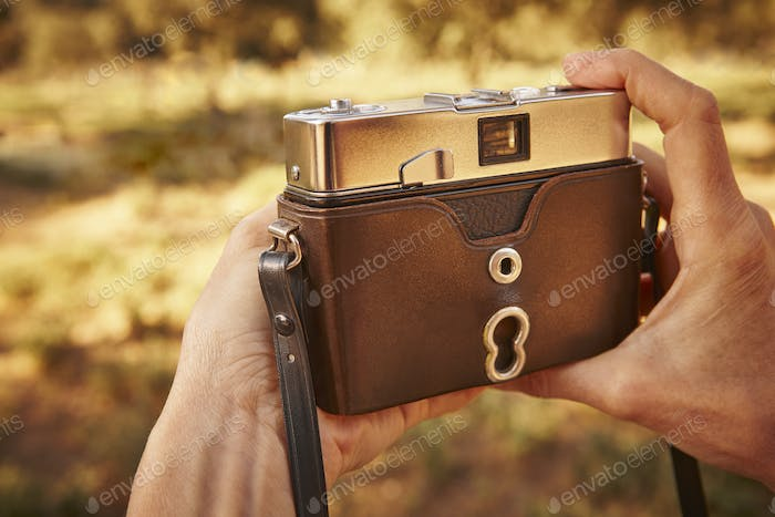 Hiker with vintage camera in the countryside. Travel background. Lifestyle
