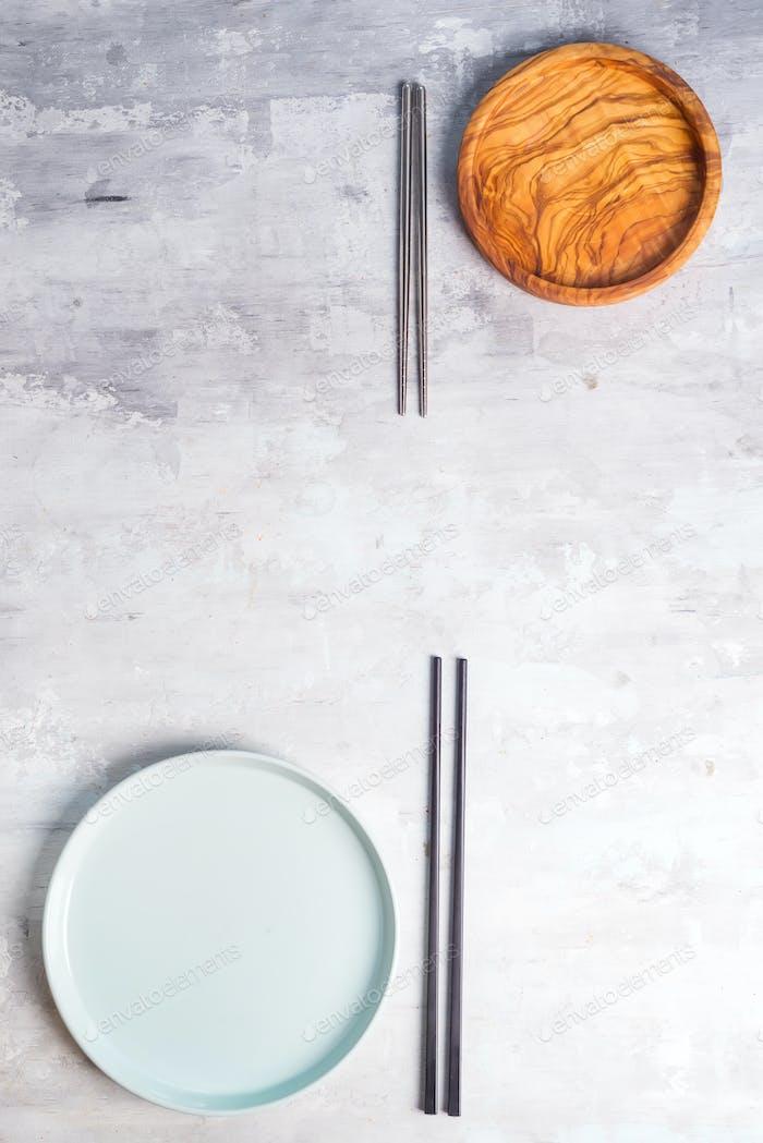 Flacher Teller und Eisenstöcke auf grauem Hintergrund. Leere Platte. , Lebensmittel, Zero-Waste Konzept