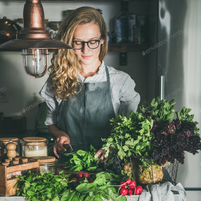 Young woman cutting herbs and vegetables in kitchen, square crop