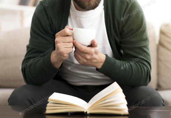 Abgeschnittenes Foto des Menschen trinken Kaffee während der Lektüre Buch