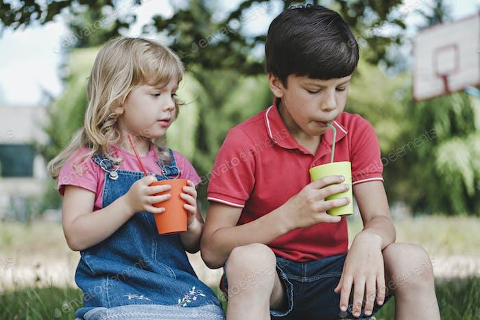 Zwei kleine Kinder genießen ein gesundes Getränk