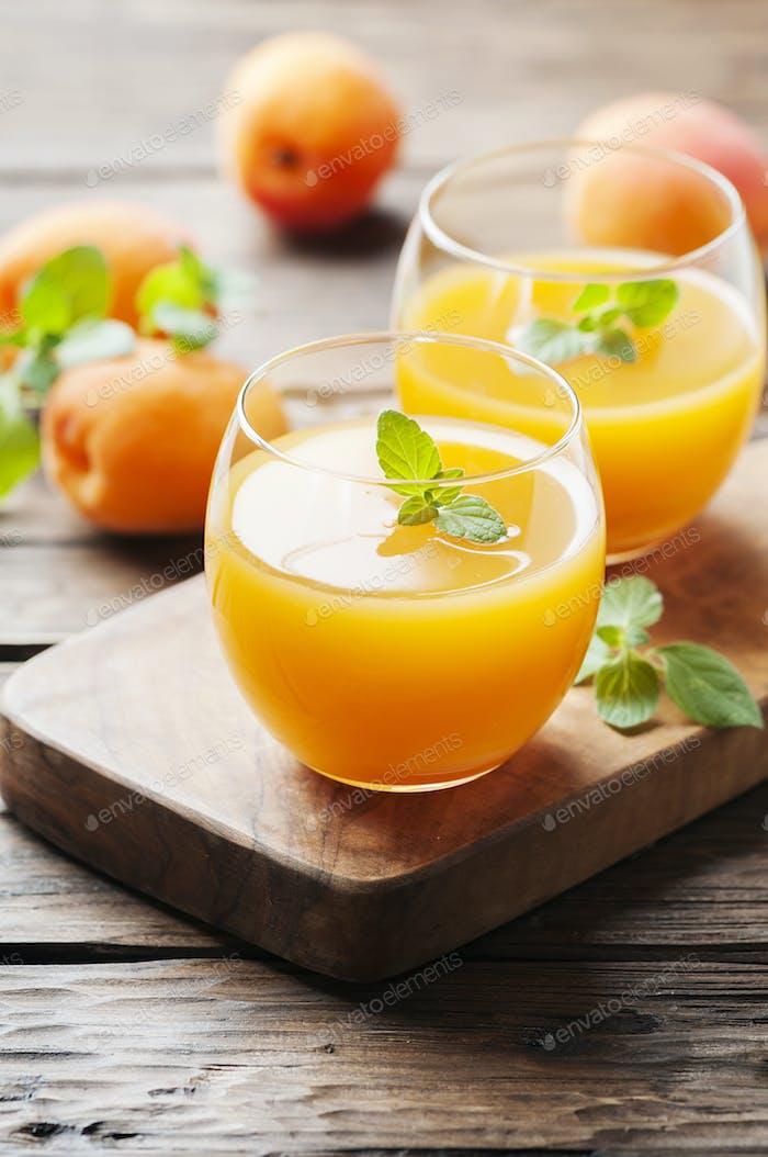 Gesunder Aprikosensaft mit Minze auf dem Holztisch