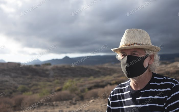 Serious senior man wearing face mask because of the Covid-19 virus. Outdoors with overcast sky