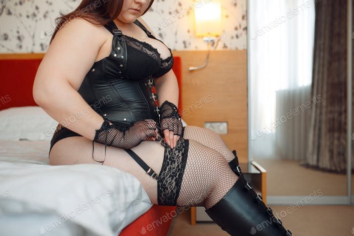 Overweight perverse woman puts on erotic lingerie