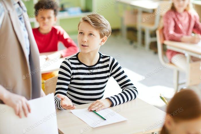 Boy asking teacher about test